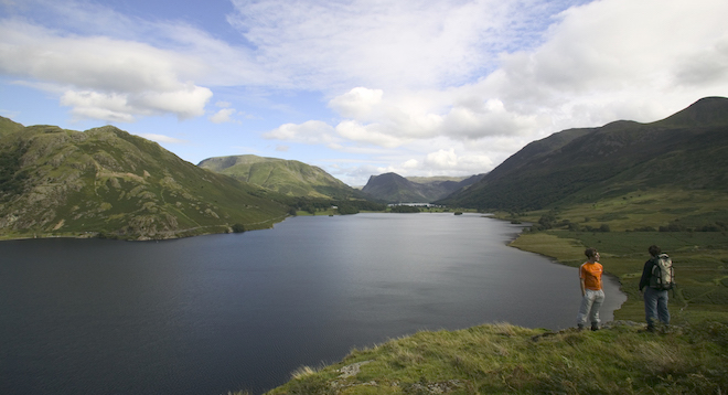 Two hikers standing next to Lake Buttermere.